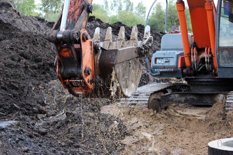 o trabalho sujo da cubeta da máquina escavadora, que escava e nivelou as colheres à terra molha em reparos da estrada imagem de stock