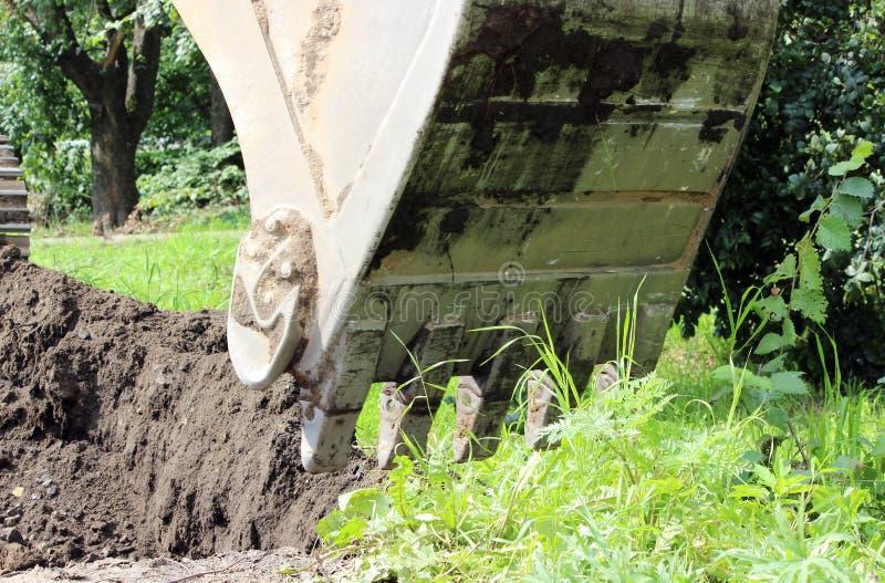 o trabalho sujo da cubeta da máquina escavadora, que escava e nivelou a terra em reparos da estrada fotos de stock