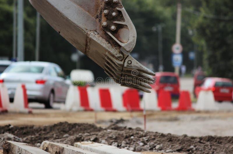 o trabalho sujo da cubeta da máquina escavadora, que escava e nivelou a terra em reparos da estrada imagem de stock