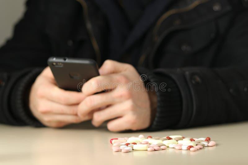 O traficante de drogas com comprimidos da êxtase chama clientes fotografia de stock royalty free