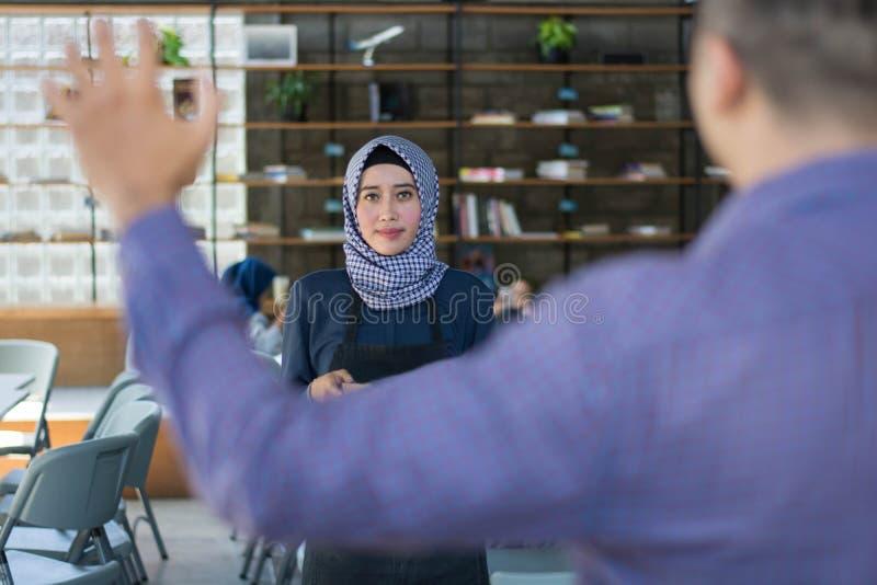 O traje masculino que chama para garçons fêmeas do café do hijab, apronta-se para a ordem imagem de stock royalty free