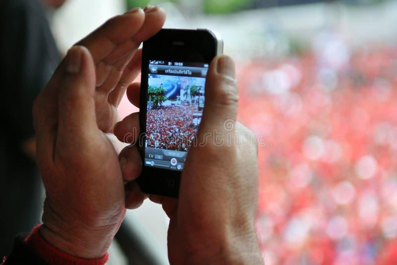 O transeunte fotografa uma reunião da Vermelho-Camisa em Banguecoque fotos de stock
