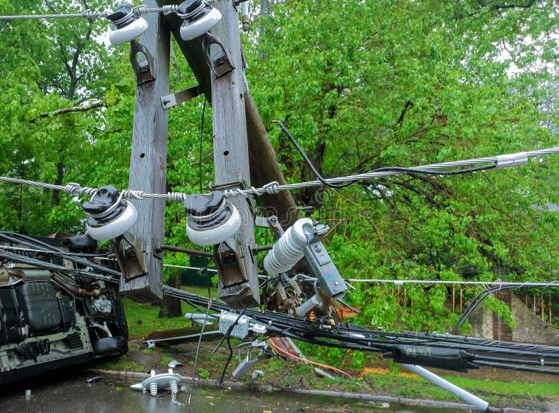 o transformador em um polo e em uma árvore que colocam através das linhas elétricas sobre uma estrada após o furacão moveu-se tra imagens de stock royalty free