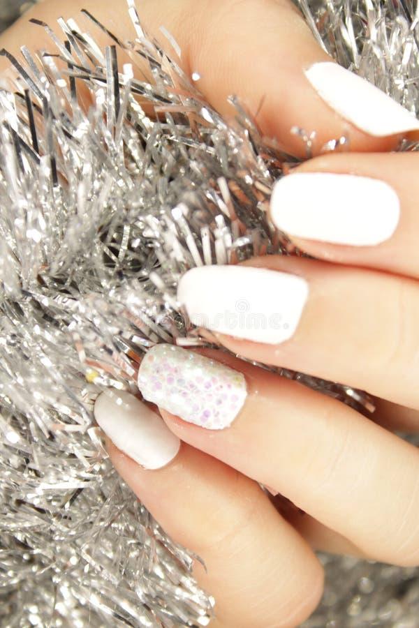 O tratamento de mãos de ano novo, cor do prego do Natal, pregos brancos da cor imagem de stock royalty free