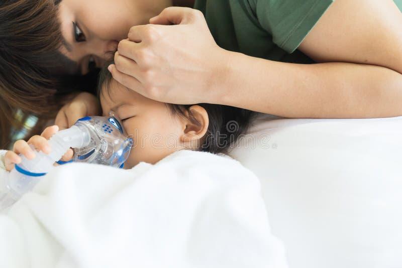 O tratamento de respiração do bebê asiático com mãe ciao, no ro foto de stock