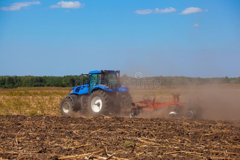 O trator azul grande ara o campo e remove as sobras do girassol previamente segado foto de stock