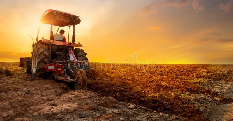 O trator está preparando o solo plantando sobre o fundo do céu do por do sol fotografia de stock