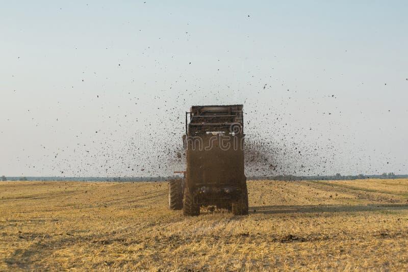 O trator fertiliza o campo com estrume Um grande reboque sowing Agroindústria Polo antes de semear De encontro ao céu foto de stock
