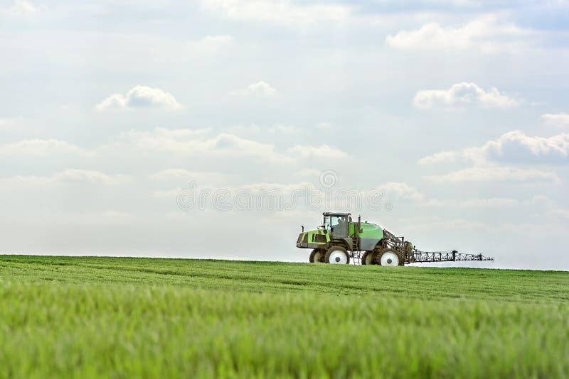 O trator fertiliza tiros do trigo foto de stock