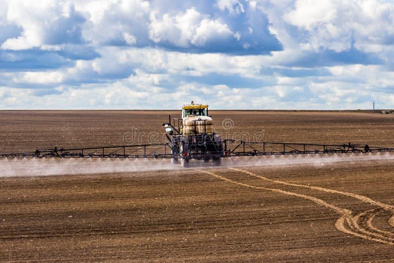 O trator que pulveriza um campo na exploração agrícola, fertiliza a terra fotografia de stock royalty free