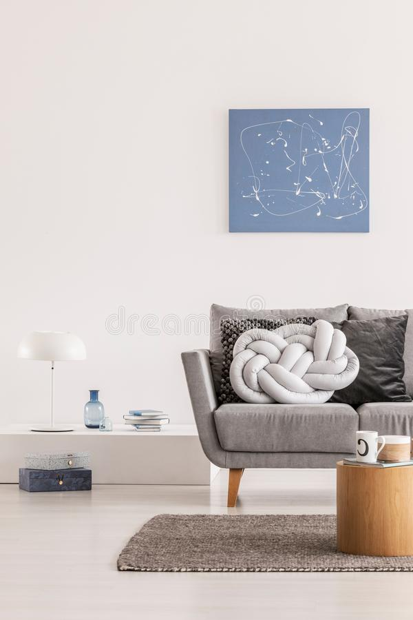O travesseiro cinza de Trendy no confortável sofá escandinavo imagens de stock