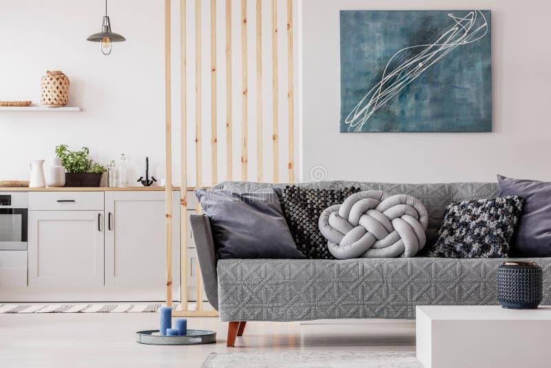 O travesseiro cinza de Trendy no confortável sofá escandinavo fotografia de stock royalty free