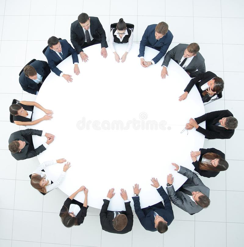 O treinador conduz a sessão com a equipe do negócio que senta-se em uma mesa redonda fotos de stock royalty free