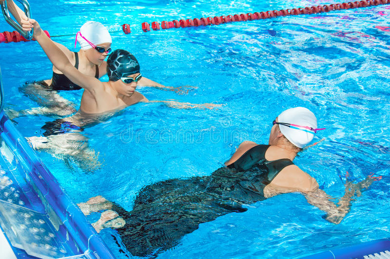 O treinador da natação mostra exercícios para crianças fotos de stock royalty free