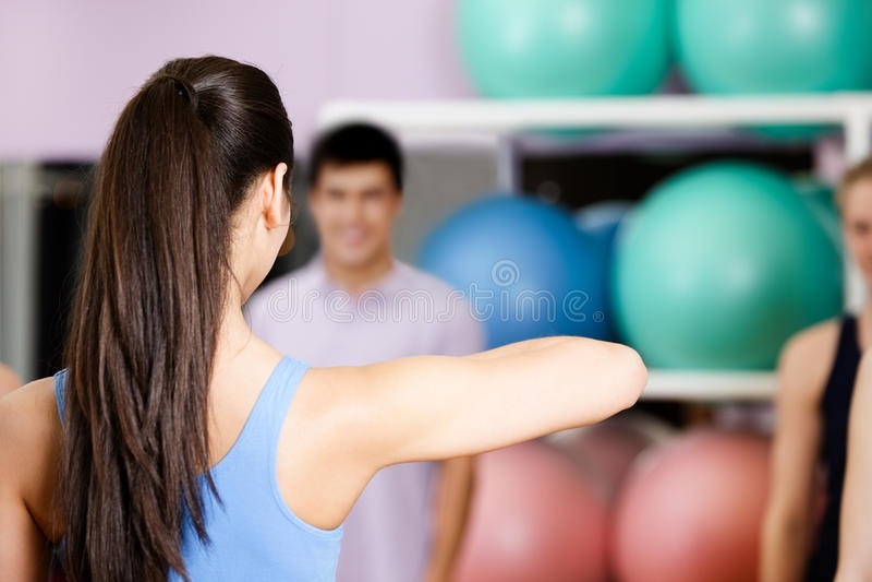 O treinador dos jovens mostra exercícios novos imagem de stock