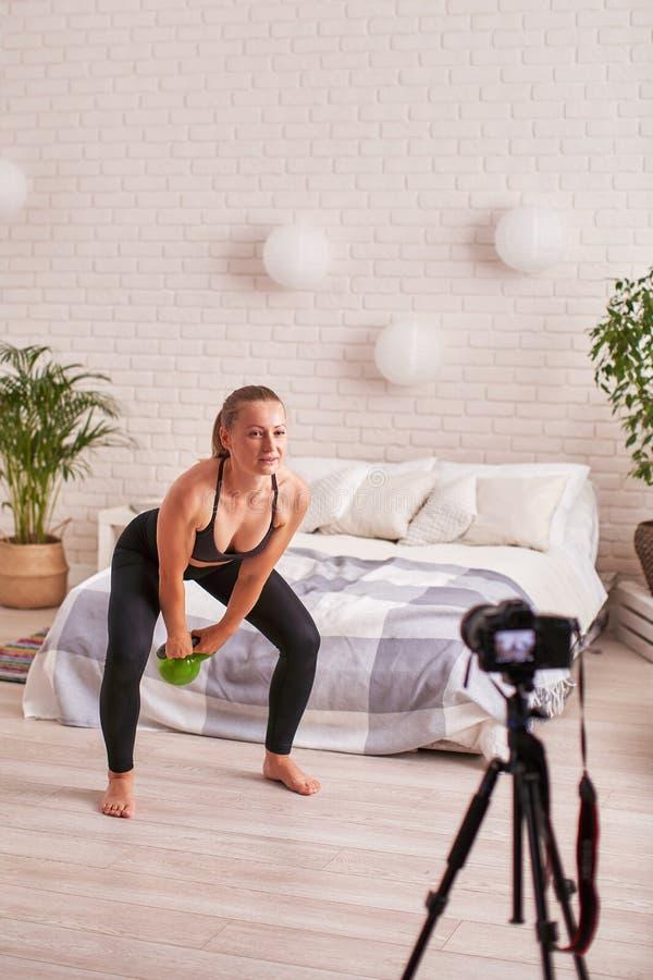 O treinador em linha da transmissão mostra a técnica de executar exercícios com os pesos treinamento dos músculos traseiros imagens de stock royalty free