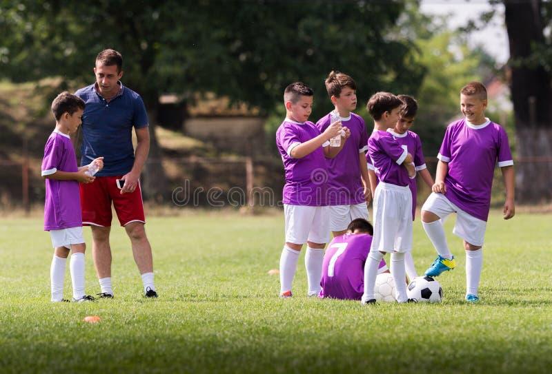 O treinador está dando o conselho aos jogadores de futebol no fósforo de futebol foto de stock royalty free