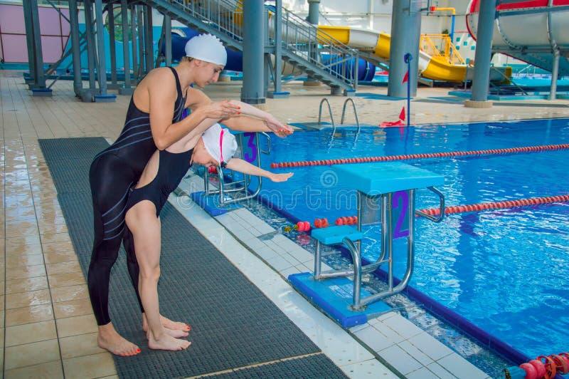 O treinador no parque da água ensina uma menina nadar foto de stock