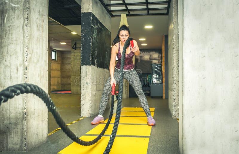 O treinamento da menina nova e atrativa bonita que faz o divertimento e as caras engraçadas quando malhar na batalha ropes no gym fotografia de stock
