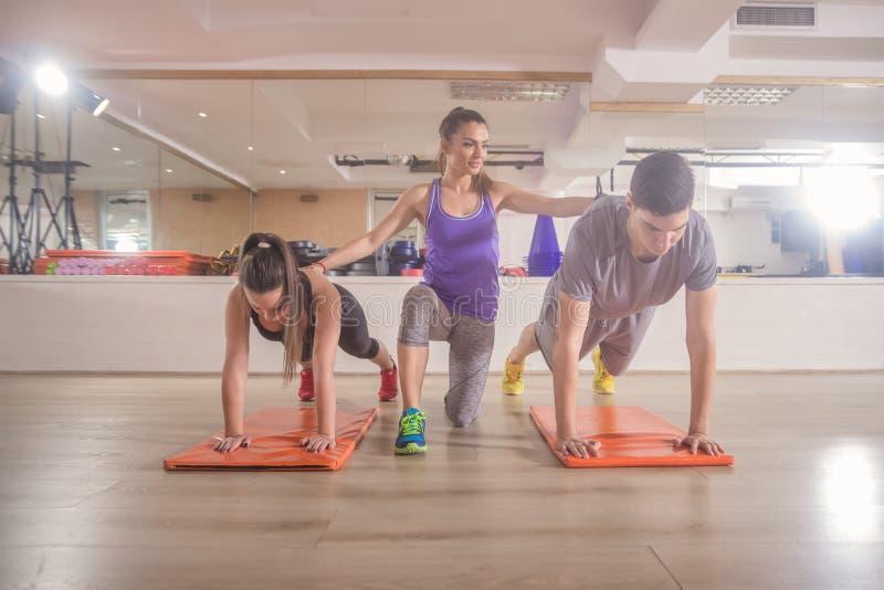 O treinamento de instrutor da aptidão levanta o gym dos povos do grupo três fotografia de stock royalty free