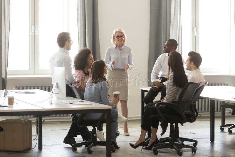 O treinamento envelhecido médio do mentor do chefe da mulher de negócios interna empregados no escritório imagens de stock