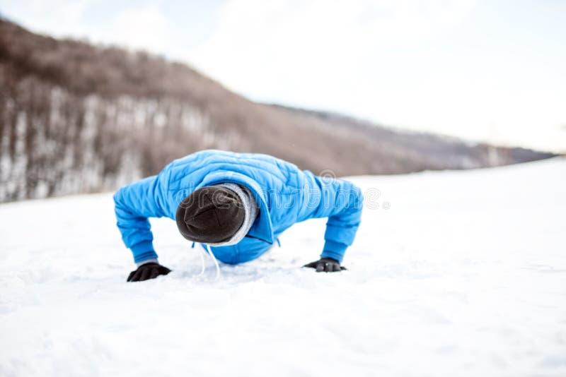 O treinamento exterior com atleta que fazer empurra levanta na neve imagens de stock royalty free