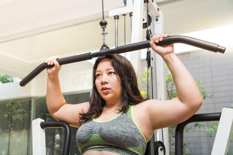 O treinamento gordo do exercício da perda de peso da mulher no lat puxa para baixo a máquina no gym da aptidão fotos de stock royalty free