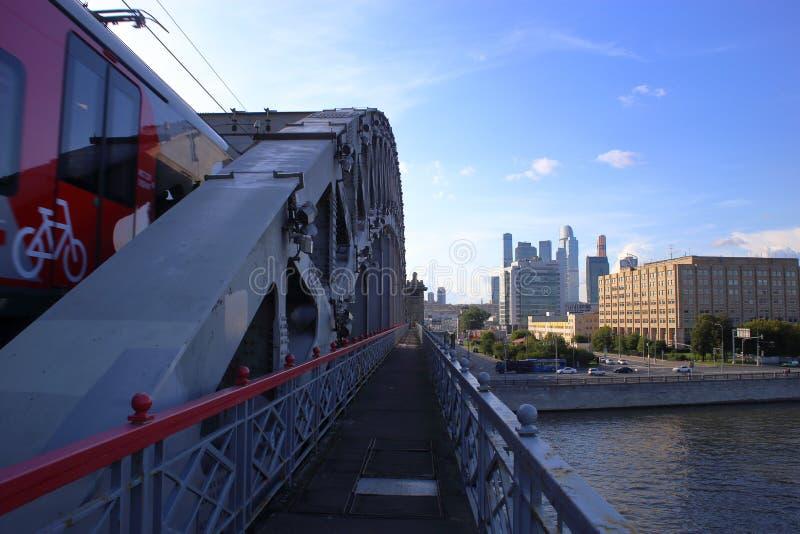 O trem atravessa a ponte de Luzhnetsky que negligencia as torres da Mosckva-cidade imagens de stock royalty free