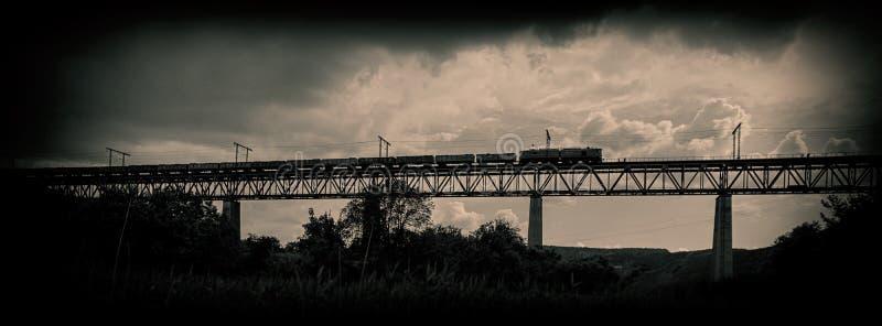 O trem de estrada de ferro move-se ao longo da ponte contra um fundo do th fotografia de stock