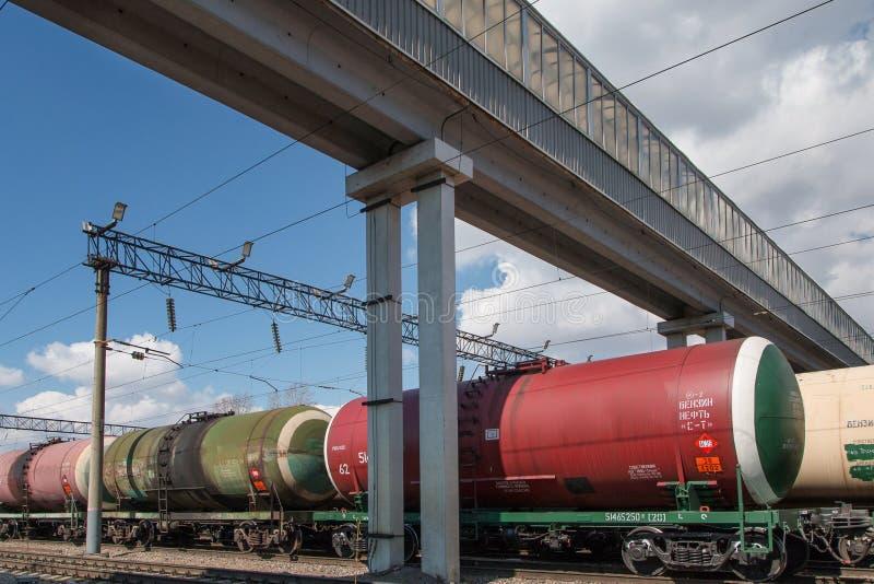 O trem de mercadorias com tanques está nos trilhos sob a passagem superior na estação de cidade Os tanques do trem com petr?leo e imagens de stock royalty free
