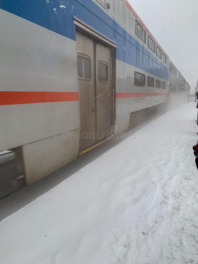O trem de Metra puxa na estação durante a tempestade de neve com montes de neve de sopro fotografia de stock royalty free