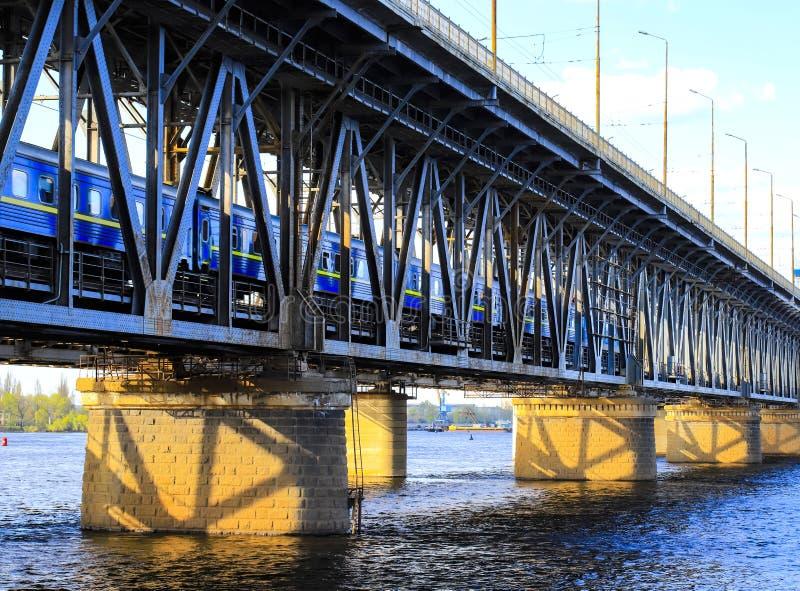 O trem de passageiros viaja ao longo de uma ponte de dois níveis e de uma estrada de ferro através do rio de Dnieper na cidade de fotos de stock