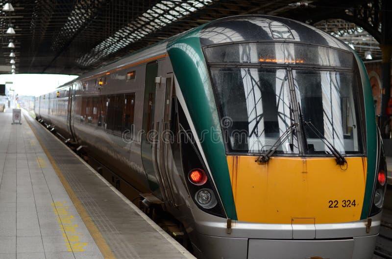 O trem irlandês amarelo e verde parou na estação imagem de stock royalty free