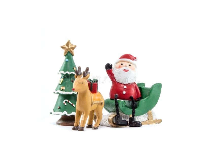 O trenó Papai Noel do verde do talão da rena senta-se gesticula sobre sua mão no fundo branco imagem de stock
