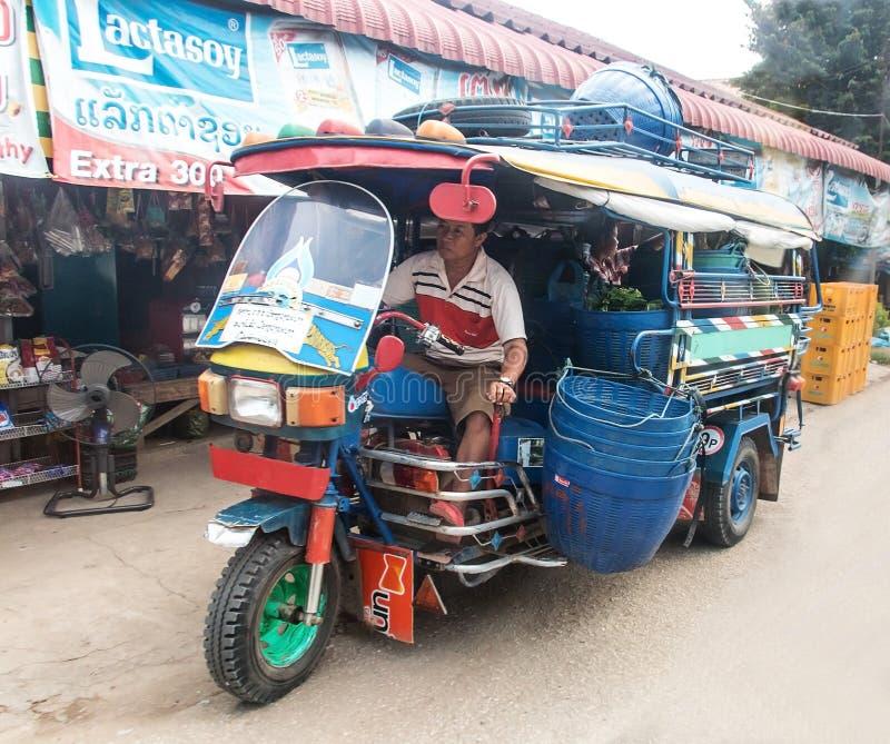 O triciclo viajado de automóvel que faz a mercadoria da entrega no mercado fotografia de stock