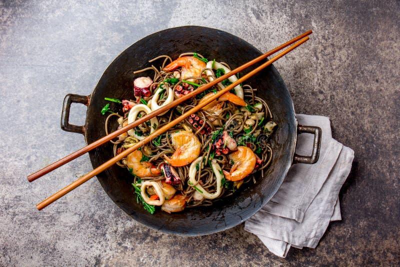O trigo mourisco frita mexendo macarronetes com marisco - camarões, polvo, calamar no frigideira chinesa asiático do ferro fundid imagens de stock royalty free