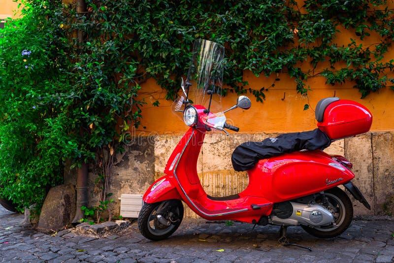 O 'trotinette' vermelho do Vespa estacionou na rua velha em Roma, Itália fotografia de stock