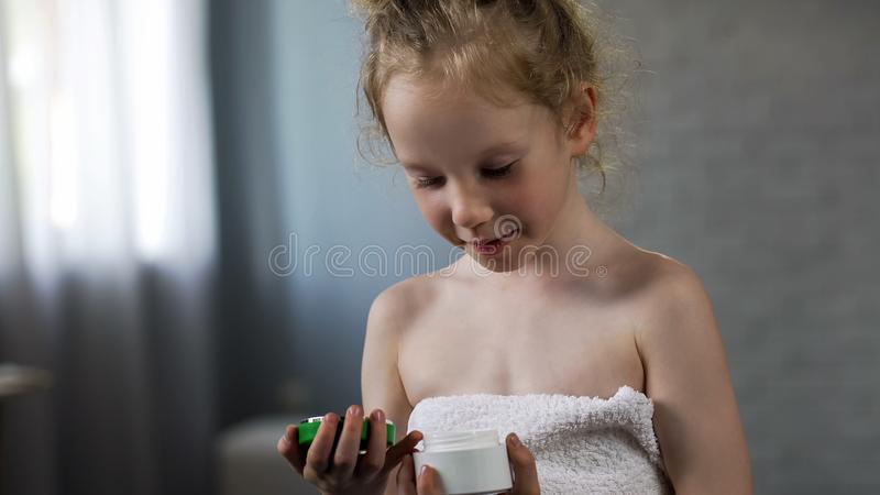 O tubo bonito entusiasmado da terra arrendada da menina com o tubo do creme das mães, preparando-se usa-o foto de stock