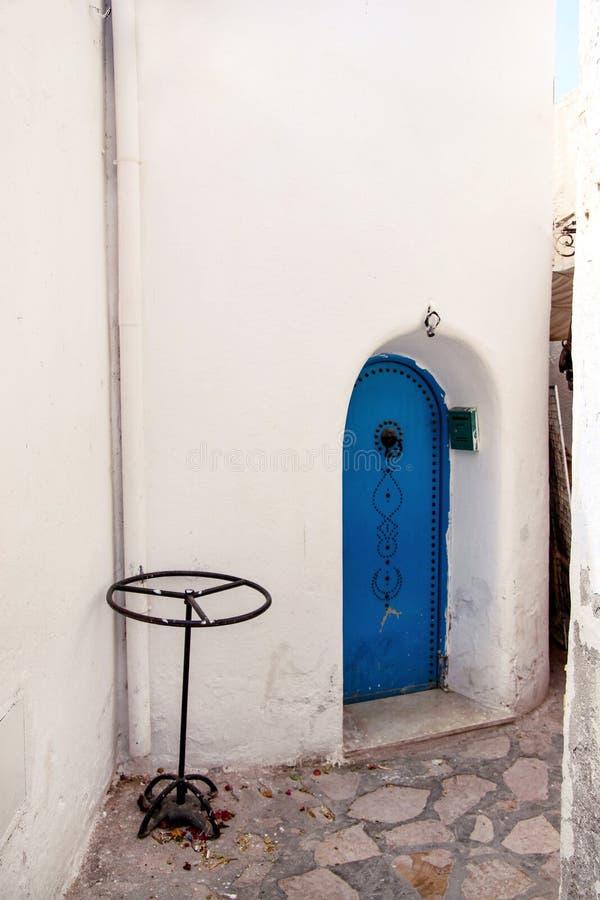 O Tunisian nacional idoso pintou a porta azul em Medina de Tunísia no Norte de África mediterrâneo da costa fotos de stock