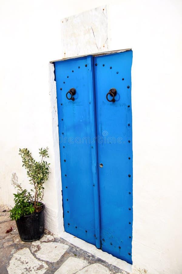 O Tunisian nacional idoso pintou a porta azul em Medina de Tunísia no Norte de África mediterrâneo da costa imagens de stock royalty free