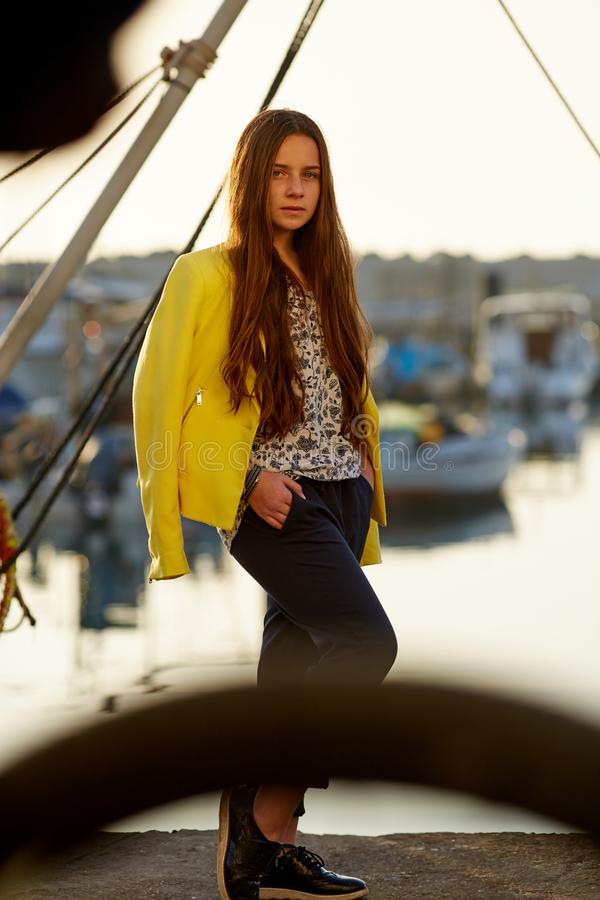 O turismo relaxam e o conceito dos povos Forme a menina loura com coração azul os óculos de sol dados forma no porto contra iate  fotos de stock
