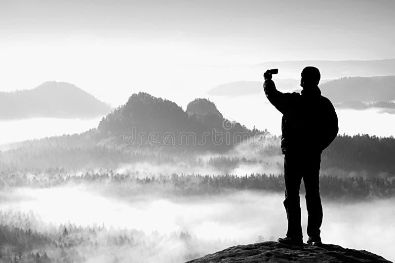 O turista alto está tomando o selfie no pico acima do vale Fotografia esperta do telefone imagens de stock