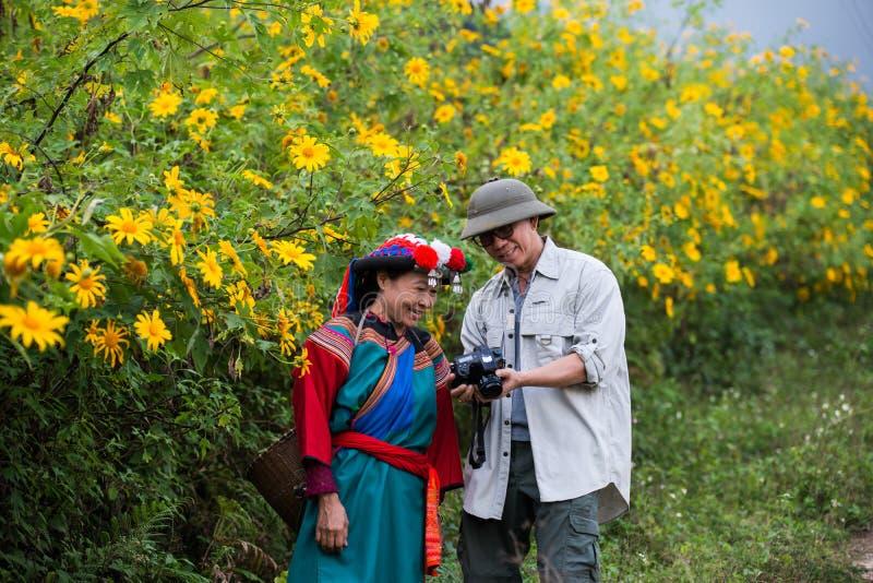 O turista aprecia o campo exterior dos girassóis da natureza da fotografia fotos de stock royalty free