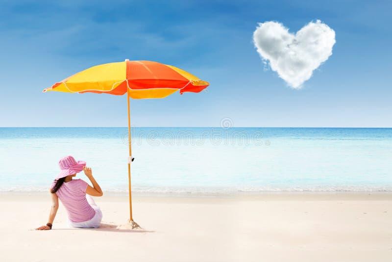 O turista asiático na praia sob o guarda-chuva e o amor nublam-se foto de stock royalty free