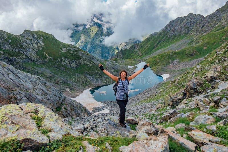 O turista bem sucedido alegre do homem com os braços aumentados na rocha em montanhas aproxima o lago frio da montanha imagem de stock