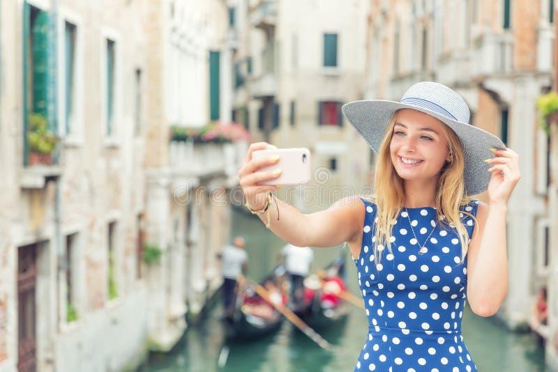 O turista bonito do viajante do gir no vestido azul do às bolinhas faz o selfie em Veneza Itália Jovem mulher loura atrativa do m imagem de stock royalty free