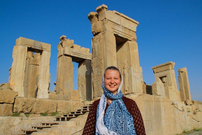 O turista da jovem mulher com uma cabeça coberta está no fundo dos bas-relevos famosos da capital de Persia Iran - P do dia imagens de stock royalty free