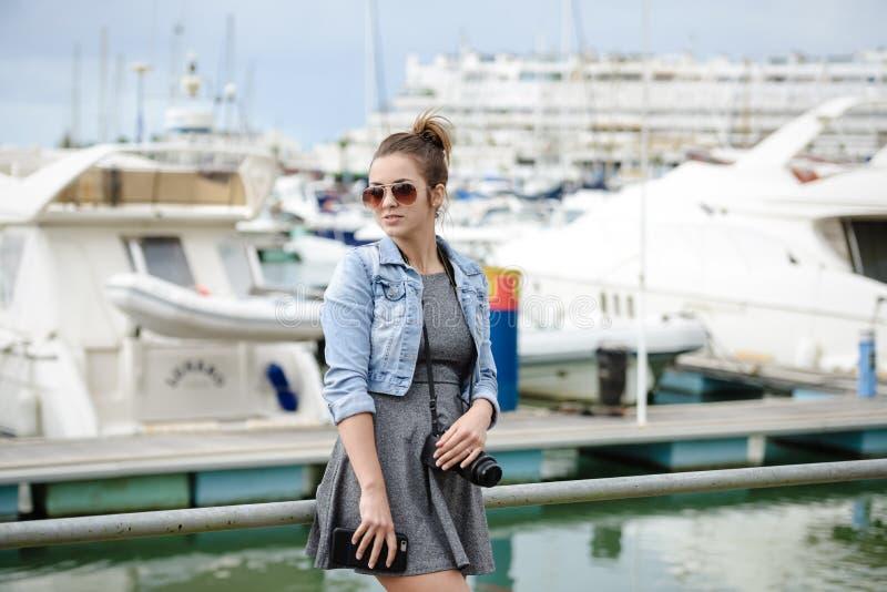 O turista da jovem senhora que guarda a câmera que está no tiro do porto yachts foto de stock