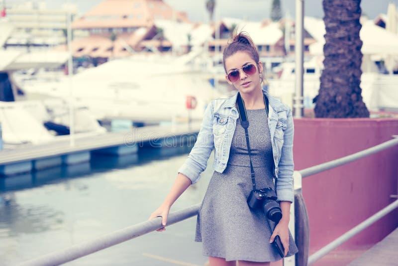O turista da jovem senhora que guarda a câmera que está no tiro do porto yachts fotos de stock royalty free