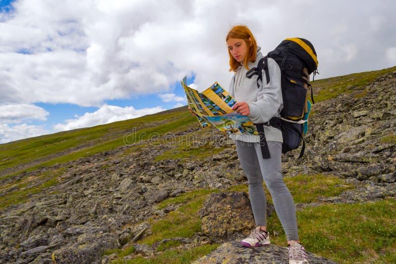 O turista da menina do ruivo que procura uma rota no mapa em seu h imagens de stock royalty free
